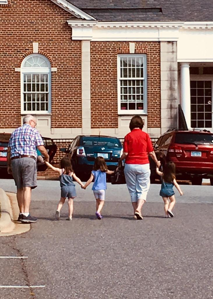 backsides of grandfather holding  hands with three small granddaughters and their grandmother in front of the library building
